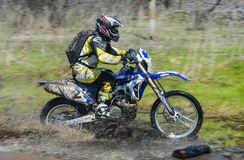 Enduro motorcycle rides through the mud with a big splash Royalty Free Stock Photography
