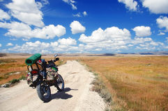 Enduro-Motorradreisender mit den Koffern, die auf einem Schotterweg stehen Stockbilder