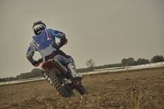 Enduro pilot on a curve. Enduro rider taken from behind while he is facing a curve with his bike in a dirt track royalty free stock image