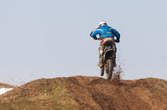 Enduro racers. With mud on motorbike climbing hill royalty free stock photo
