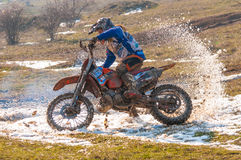 Enduro racers. With mud on motorbike skidding on snow royalty free stock photos
