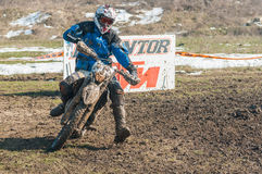 Enduro racers. Enduro racer with mud on motorbike in front of KTM Dementor billboard Stock Photos