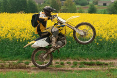 Enduro rider. Man on motocross enjoying ride. Yellow meadow at the background Royalty Free Stock Image