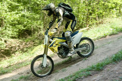 Enduro Rider. Angled side view of an enduro rider in a standing position on a moving cycle Royalty Free Stock Photos