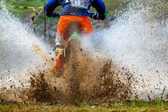 Enduro rides through the mud with big splash,driver splashing mud on wet and muddy terrain royalty free stock images