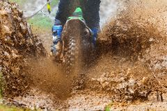Enduro rides through the mud with big splash. royalty free stock photos
