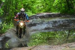 Enduromoto in de modder met een grote plons Royalty-vrije Stock Foto's