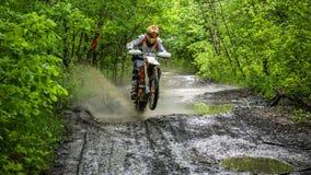 Enduromoto in de modder met een grote plons Stock Afbeelding