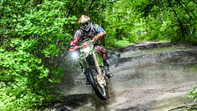 Enduromoto in de modder met een grote plons Stock Foto's