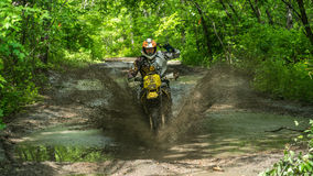 Enduromoto in de modder met een grote plons Stock Foto