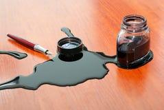 Enegreça o derramamento da tinta perto da pena vermelha na tabela Imagem de Stock