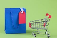 Enegreça sexta-feira Preços de compra para a venda no pacote e no trole de compra em um fundo verde fotografia de stock royalty free
