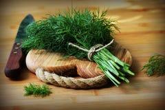 Eneldo orgánico fresco para encendido la tabla de cortar de madera puesta cocinero con el cuchillo Imagen de archivo