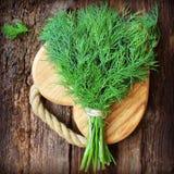 Eneldo orgánico fresco para encendido la tabla de cortar de madera puesta cocinero Imagenes de archivo
