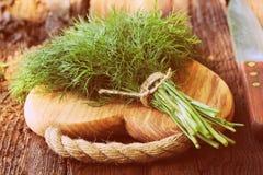 Eneldo orgánico fresco para encendido la tabla de cortar de madera puesta cocinero con el cuchillo Imágenes de archivo libres de regalías