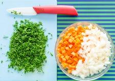 Eneldo tajado, cebolla, zanahorias Cuchillo de cerámica, tablero azul Fotografía de archivo