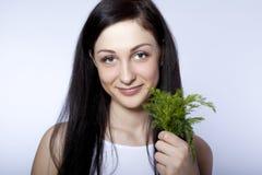 eneldo verde sonriente hermoso de la explotación agrícola de la mujer joven Foto de archivo libre de regalías