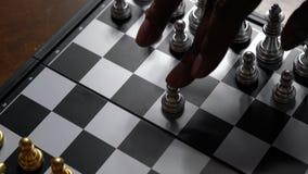 Enemigo de mudanza de la derrota del empe?o del ajedrez de la mano en el tablero de ajedrez almacen de metraje de vídeo