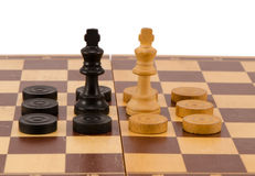 Enemy chess queen surround checkers board isolated. Enemy chess queens stand in front surrounded by checkers on wooden board isolated on white Stock Images