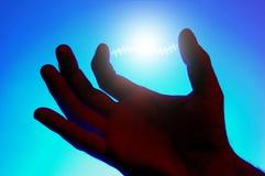 Energía que brilla intensamente entre los dedos Foto de archivo