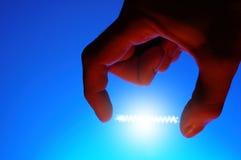 Energía que brilla intensamente entre los dedos Fotos de archivo libres de regalías