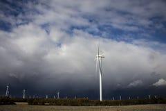 Energía renovable del molino de viento con las nubes profundas del cielo azul Fotos de archivo