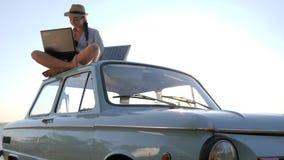Energía renovable, sentada femenina en el coche clásico del vintage con el cuaderno y batería en el cielo del fondo en luz del so