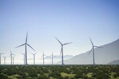 Energía solar del molino de viento con la hierba y las montañas Imagen de archivo libre de regalías