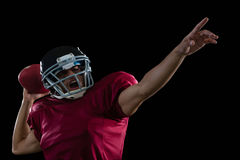 Energetic American football player aiming a ball. Against a black background royalty free stock images