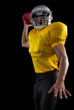 Energetic American football player holding a ball in one hand. Against a black background royalty free stock photo