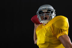 Energetic American football player holding a ball in one hand. Against a black background royalty free stock photos