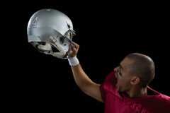 Energetic American football player holding a head gear raised. Against a black background royalty free stock photography