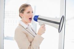 Energetic blonde businesswoman shouting in megaphone Stock Photo
