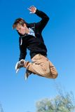 Energetic boy jumping. Close up portrait of energetic boy jumping outdoors royalty free stock photography