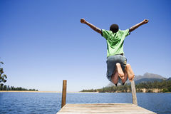 Energetic boy (8-10) jumping on lake jetty, arms out, rear view Royalty Free Stock Photo