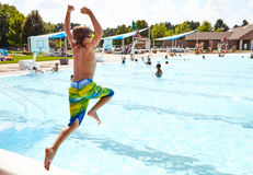 Energetic boy jumping in outdoor swimming pool. Rear view of energetic little Caucasian boy jumping in outdoor swimming pool. Boy resting at summer resort by royalty free stock photography
