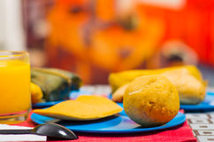 An energetic breakfast contain orange juice, empanada and bolon served on a blue plate, traditional andean food concept Stock Photos