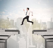 Energetic business man jumping over a bridge with gap Stock Photography