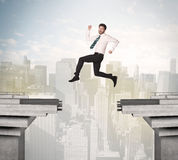 Energetic business man jumping over a bridge with gap. Concept Royalty Free Stock Photography