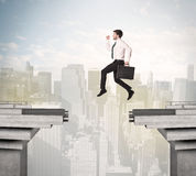 Energetic business man jumping over a bridge with gap. Concept Stock Image