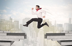 Energetic business man jumping over a bridge with gap Royalty Free Stock Image