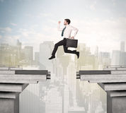 Energetic business man jumping over a bridge with gap. Concept Royalty Free Stock Photo