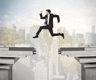 Energetic business man jumping over a bridge with gap Royalty Free Stock Photo