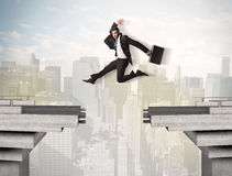 Energetic business man jumping over a bridge with gap Stock Photos