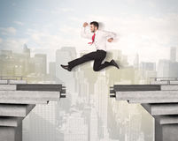 Energetic business man jumping over a bridge with gap. Concept Stock Photo
