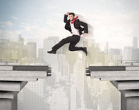 Energetic business man jumping over a bridge with gap. Concept Stock Images