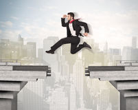 Energetic business man jumping over a bridge with gap. Concept Royalty Free Stock Images