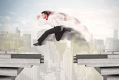 Energetic business man jumping over a bridge with gap Royalty Free Stock Images