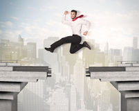 Energetic business man jumping over a bridge with gap. Concept Royalty Free Stock Image