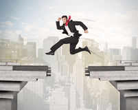 Energetic business man jumping over a bridge with gap. Concept Stock Photography